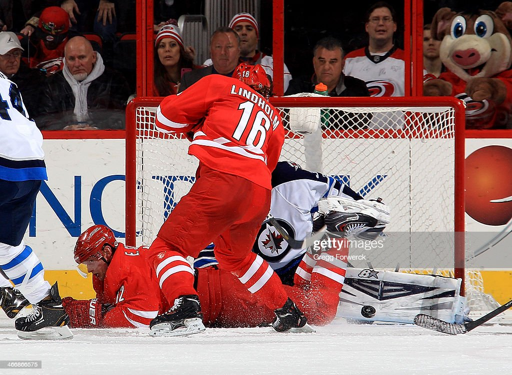 <a gi-track='captionPersonalityLinkClicked' href=/galleries/search?phrase=Eric+Staal&family=editorial&specificpeople=202199 ng-click='$event.stopPropagation()'>Eric Staal</a> #12 of the Carolina Hurricanes goes down in front of the net as goalie Ondrej Pavelec #31 of the Winnipeg Jets makes a pad save on a shot by <a gi-track='captionPersonalityLinkClicked' href=/galleries/search?phrase=Elias+Lindholm&family=editorial&specificpeople=8613151 ng-click='$event.stopPropagation()'>Elias Lindholm</a> #16 of the Hurricanes during an NHL game at PNC Arena on February 4, 2014 in Raleigh, North Carolina.
