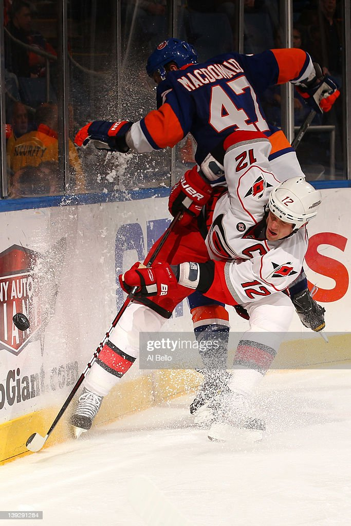 <a gi-track='captionPersonalityLinkClicked' href=/galleries/search?phrase=Eric+Staal&family=editorial&specificpeople=202199 ng-click='$event.stopPropagation()'>Eric Staal</a> #12 of the Carolina Hurricanes is checked by Andrew MacDonald #47 of the New York Islanders during their game on February 18, 2012 at the Nassau Coliseum in Uniondale, New York.