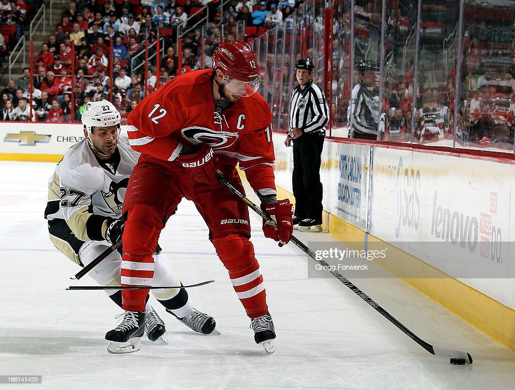 <a gi-track='captionPersonalityLinkClicked' href=/galleries/search?phrase=Eric+Staal&family=editorial&specificpeople=202199 ng-click='$event.stopPropagation()'>Eric Staal</a> #12 of the Carolina Hurricanes is slashed by <a gi-track='captionPersonalityLinkClicked' href=/galleries/search?phrase=Craig+Adams&family=editorial&specificpeople=211144 ng-click='$event.stopPropagation()'>Craig Adams</a> #27 of the Pittsburgh Penguins leading to a 5-on-3 power play for the Hurricanes during their NHL game at PNC Arena on October 28, 2013 in Raleigh, North Carolina.