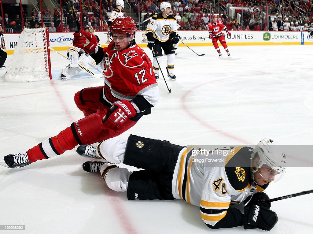 Eric Staal #12 of the Carolina Hurricanes loses his edge as he and David Krejci #46 of the Boston Bruins chase down a loose puck during their NHL game at PNC Arena on April 13, 2013 in Raleigh, North Carolina.