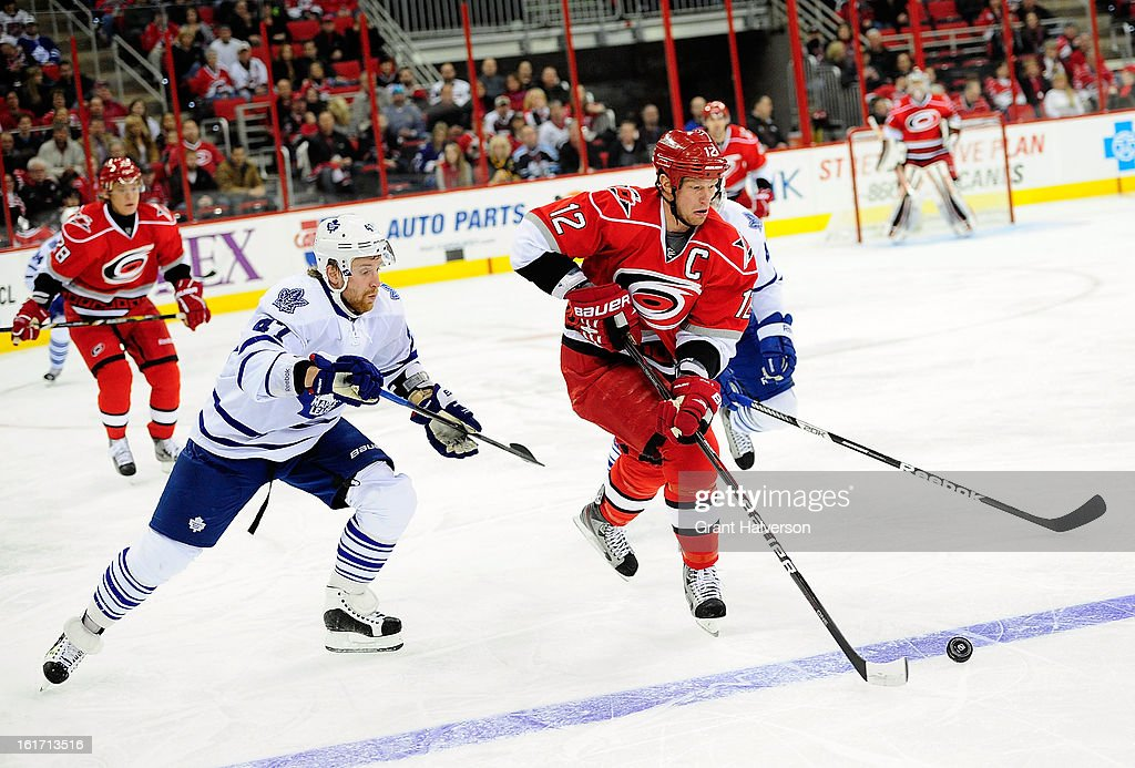 Eric Staal #12 of the Carolina Hurricanes moves the puck against Leo Komarov #47 of the Toronto Maple Leafs during play at PNC Arena on February 14, 2013 in Raleigh, North Carolina.
