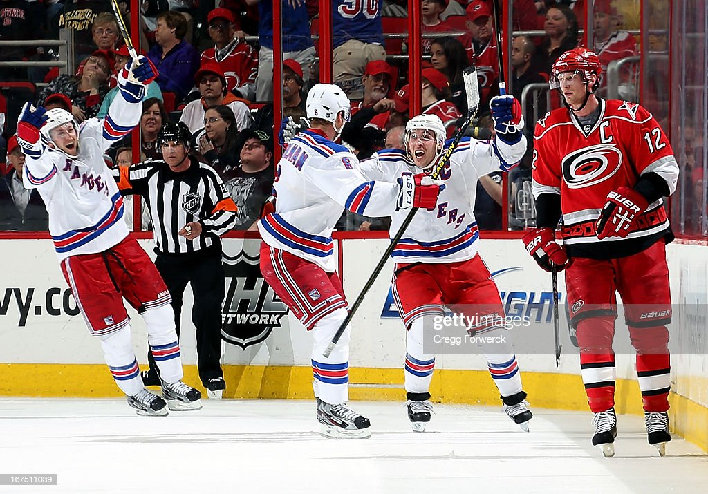 Eric Staal #12 of the Carolina Hurricanes skates past Derek Stepan #21 and Anton Stralman #6 of the New York Rangers as they celebrate an overtime game-winning goal scored by Ryan Callahan #24 during their NHL game at PNC Arena on April 25, 2013 in Raleigh, North Carolina.
