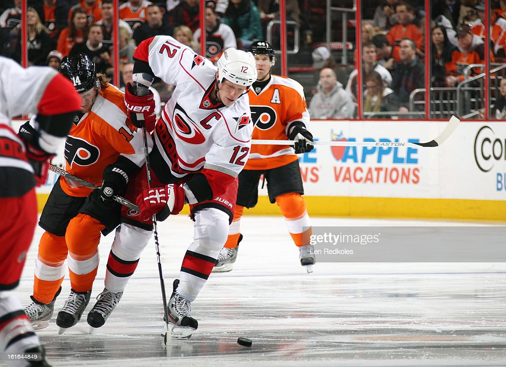 Eric Staal #12 of the Carolina Hurricanes skates the puck against Sean Couturier #14 of the Philadelphia Flyers on February 9, 2013 at the Wells Fargo Center in Philadelphia, Pennsylvania.
