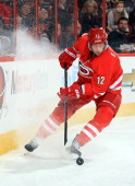 Eric Staal of the Carolina Hurricanes stops hard on the ice to control the puck against the Buffalo Sabres during their NHL game at PNC Arena on...