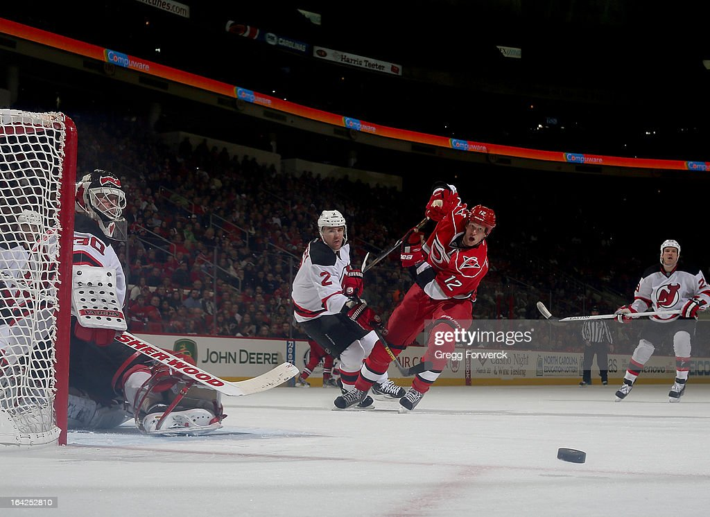 <a gi-track='captionPersonalityLinkClicked' href=/galleries/search?phrase=Eric+Staal&family=editorial&specificpeople=202199 ng-click='$event.stopPropagation()'>Eric Staal</a> #12 of the Carolina Hurricanes takes a shot on goal that is blockered away by <a gi-track='captionPersonalityLinkClicked' href=/galleries/search?phrase=Martin+Brodeur&family=editorial&specificpeople=201594 ng-click='$event.stopPropagation()'>Martin Brodeur</a> #30 of the New Jersey Devils during their NHL game at PNC Arena on March 21, 2013 in Raleigh, North Carolina.