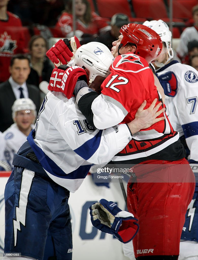 Eric Staal #12 of the Carolina Hurricanes ties up with Adam Hall #18 of the Tampa Bay Lightning during an NHL game on January 22, 2013 at PNC Arena in Raleigh, North Carolina.