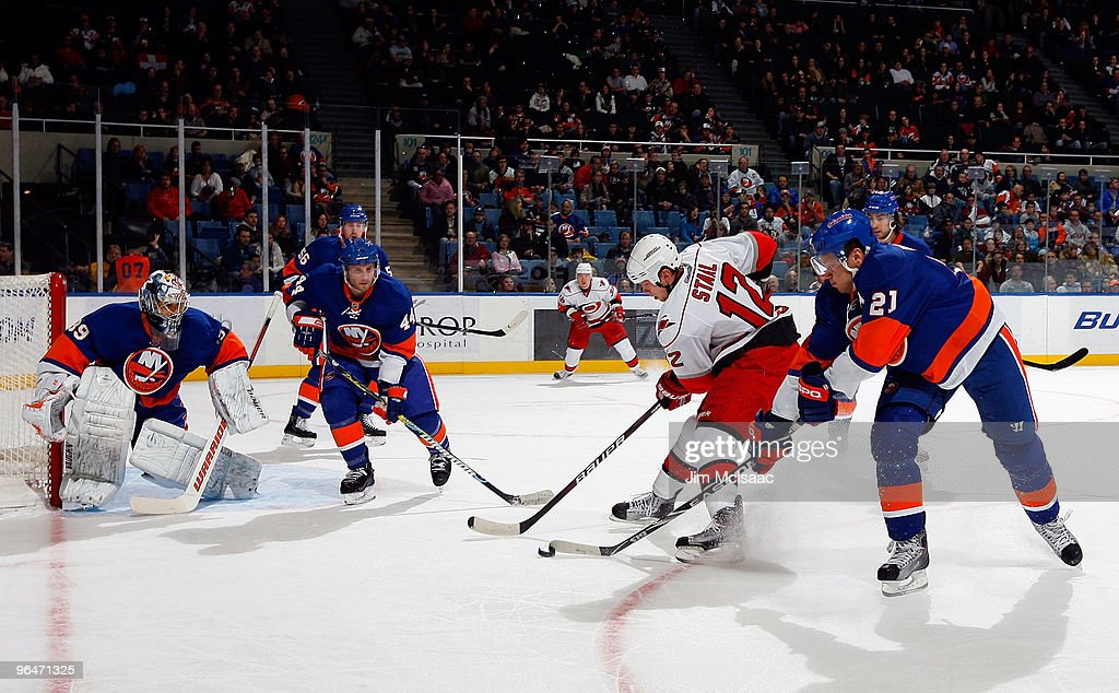 Eric Staal of the Carolina Hurricanes tries to control the puck as Kyle Okposo Rick DiPietro and Freddy Meyer of the New York Islanders defend on...
