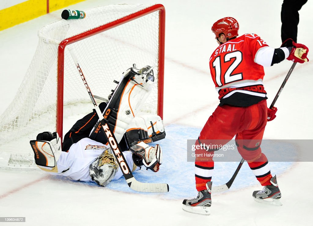 <a gi-track='captionPersonalityLinkClicked' href=/galleries/search?phrase=Eric+Staal&family=editorial&specificpeople=202199 ng-click='$event.stopPropagation()'>Eric Staal</a> #12 of the Carolina Hurricanes upends goaltender <a gi-track='captionPersonalityLinkClicked' href=/galleries/search?phrase=Jonas+Hiller&family=editorial&specificpeople=743364 ng-click='$event.stopPropagation()'>Jonas Hiller</a> #1 of the Anaheim Ducks at the RBC Center on February 23, 2012 in Raleigh, North Carolina. Anaheim won 3-2 in a shootout.