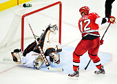 Eric Staal of the Carolina Hurricanes upends goaltender Jonas Hiller of the Anaheim Ducks at the RBC Center on February 23 2012 in Raleigh North...