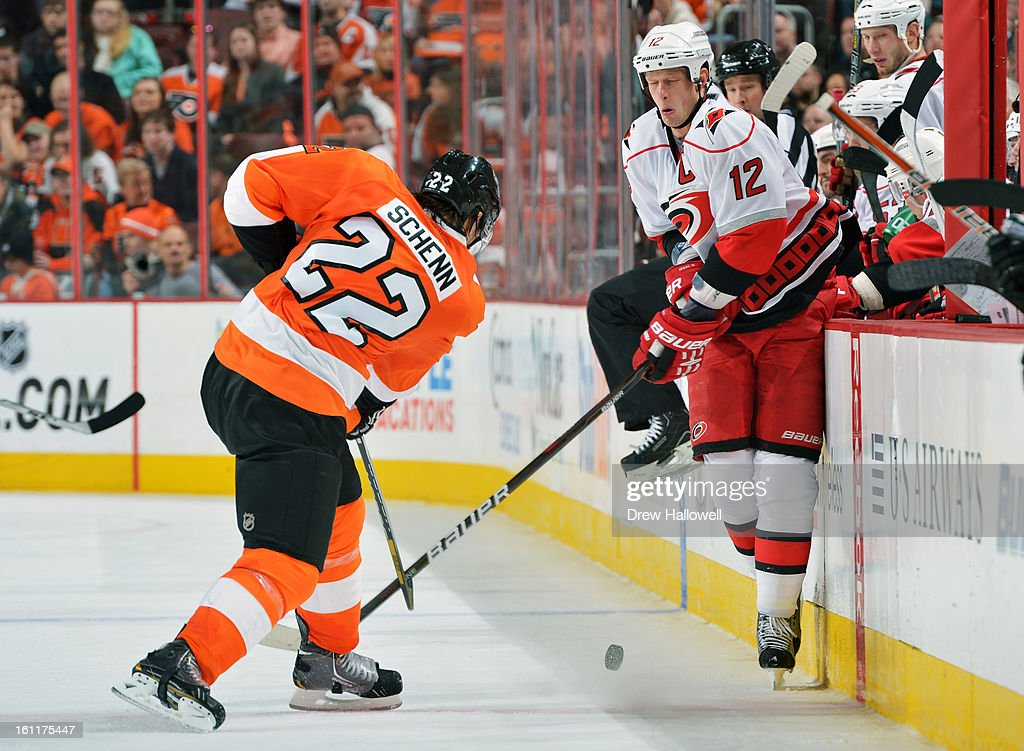 Eric Staal #12 of the Carolina Hurricanes winces as Luke Schenn #22 of the Philadelphia Flyers fires the puck down the ice at the Wells Fargo Center on February 9, 2013 in Philadelphia, Pennsylvania. The Flyers won 4-3 in overtime.