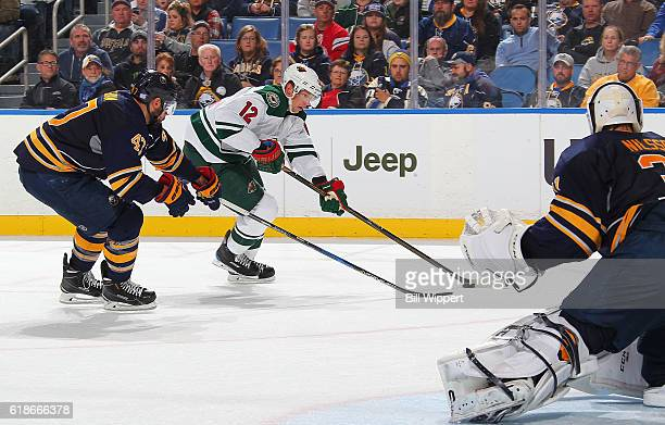 Eric Staal of the Minnesota Wild looks to shoot the puck while defended by Zach Bogosian and Anders Nilsson of the Buffalo Sabres during an NHL game...