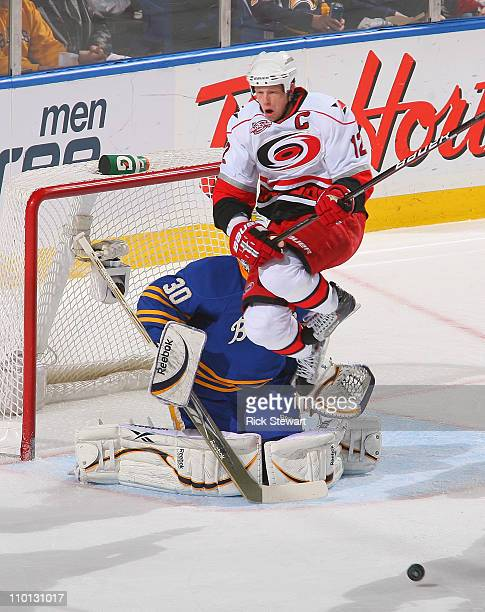 Eric Staal of the the Carolina Hurricanes jumps in front of Ryan Miller of Buffalo Sabres at HSBC Arena on March 15 2011 in Buffalo New York