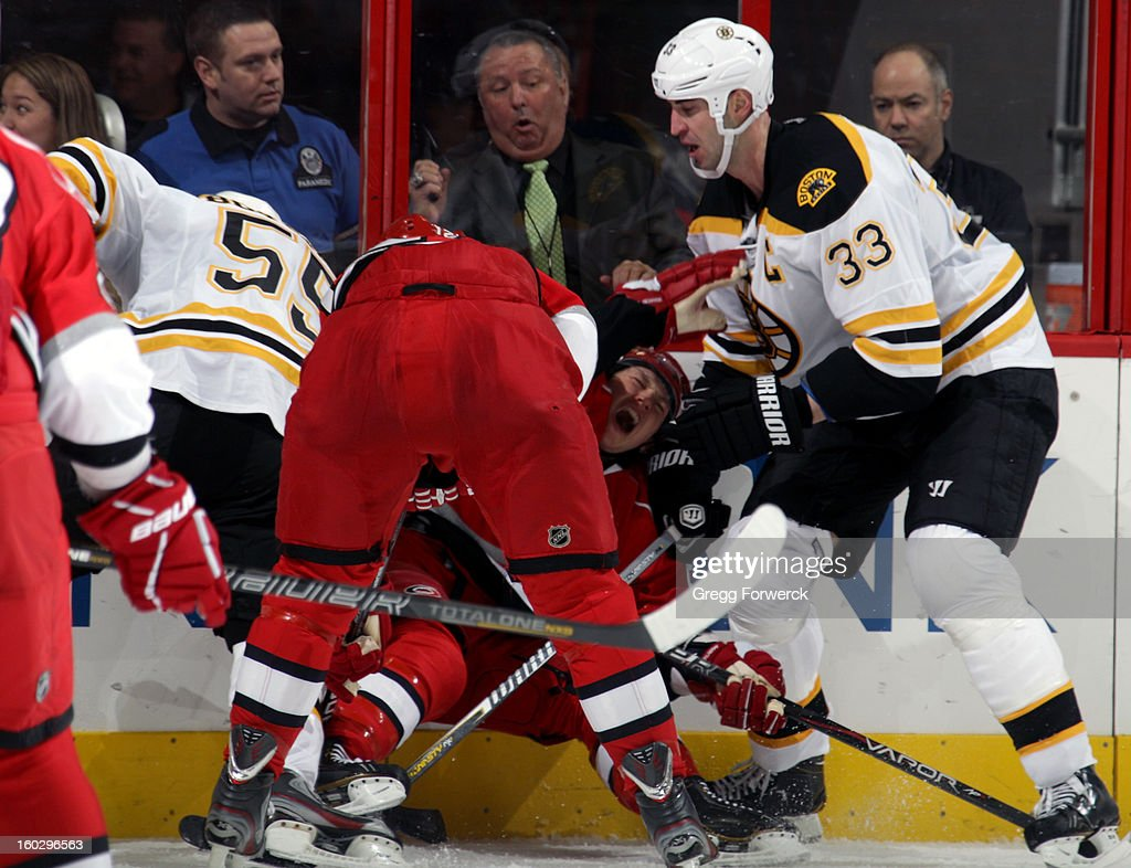 Eric Staal skates into the pileup as Jeff SKinner #53 of the Carolina Hurricanes is pinned against the boards between Johnny Boychuk #55 and Zdeno Chara #33 of the Boston Bruins during their NHL game on January 28, 2013 at PNC Arena in Raleigh North Carolina.