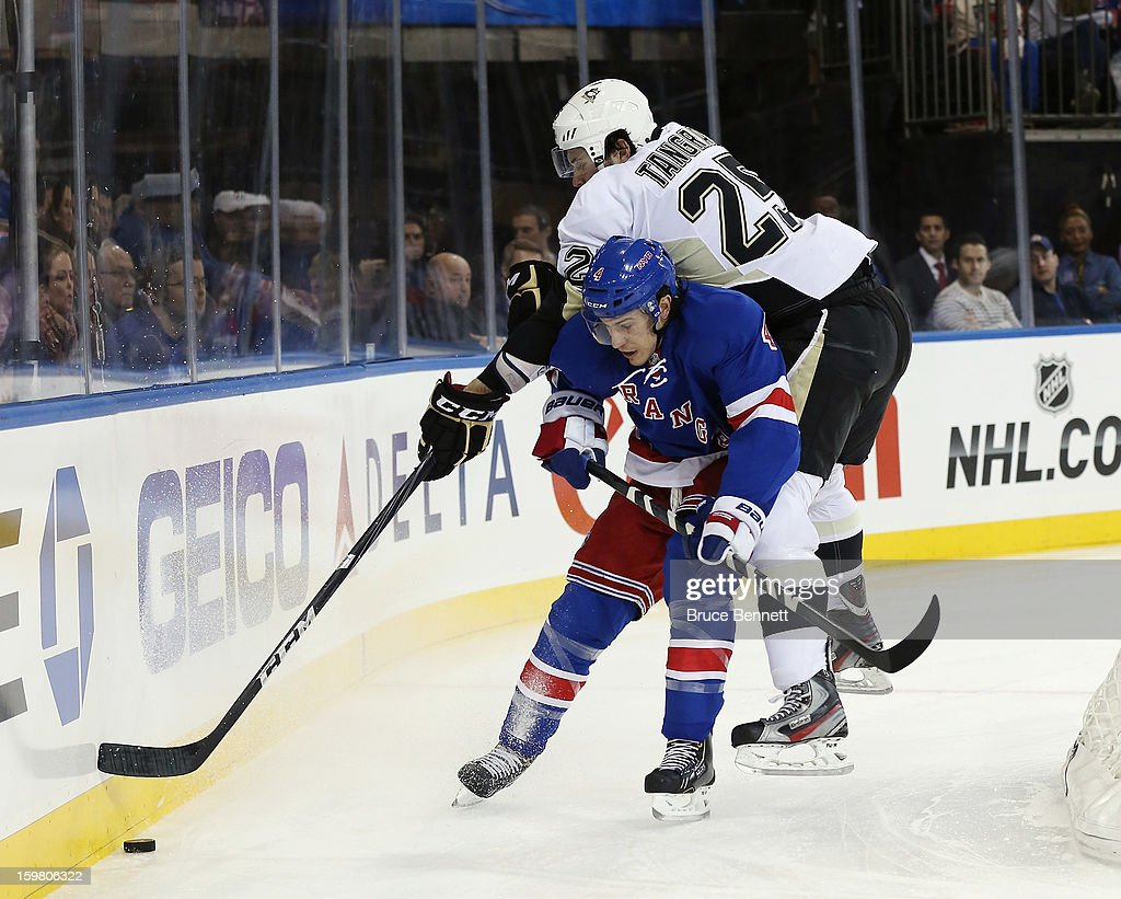 Eric Tangradi #25 of the Pittsburgh Penguins reaches over Michael Del Zotto #4 of the New York Rangers at Madison Square Garden on January 20, 2013 in New York City. The Penguins defeated the Rangers 6-3.