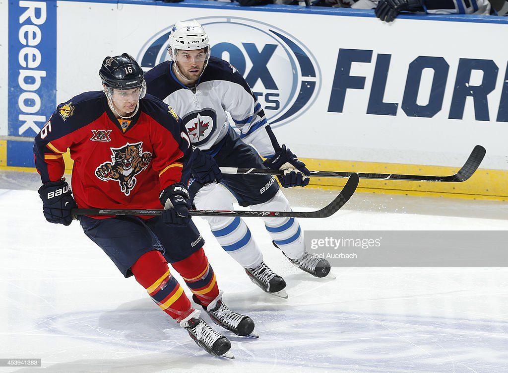 Eric Tangradi #27 of the Winnipeg Jets and Aleksander Barkov #16 of the Florida Panthers skate through center ice at the BB&T Center on December 5, 2013 in Sunrise, Florida. The Panthers defeated the Jets 5-2.