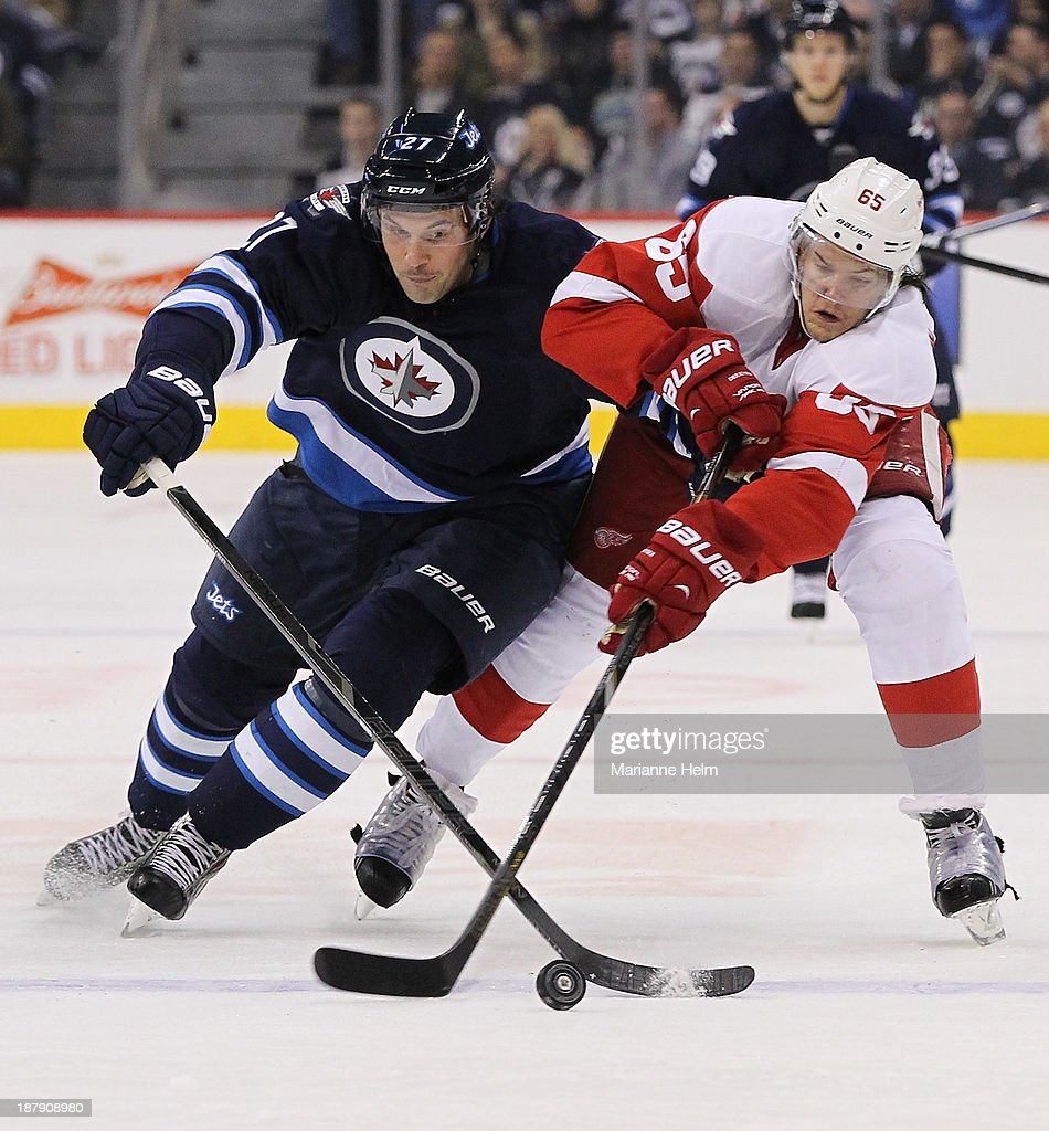 <a gi-track='captionPersonalityLinkClicked' href=/galleries/search?phrase=Eric+Tangradi&family=editorial&specificpeople=4361715 ng-click='$event.stopPropagation()'>Eric Tangradi</a> #27 of the Winnipeg Jets battles for the puck against Danny DeKeyser #65 of the Detroit Red Wings during second-period action in an NHL game at the MTS Centre on November 4, 2013 in Winnipeg, Manitoba, Canada.