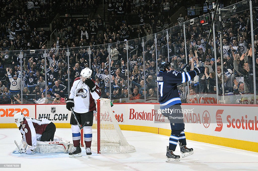 Eric Tangradi #27 of the Winnipeg Jets celebrates his first-period goal as goaltender Reto Barra #20 and Nick Holden #2 of the Colorado Avalanche react at the MTS Centre on March 19, 2014 in Winnipeg, Manitoba, Canada.