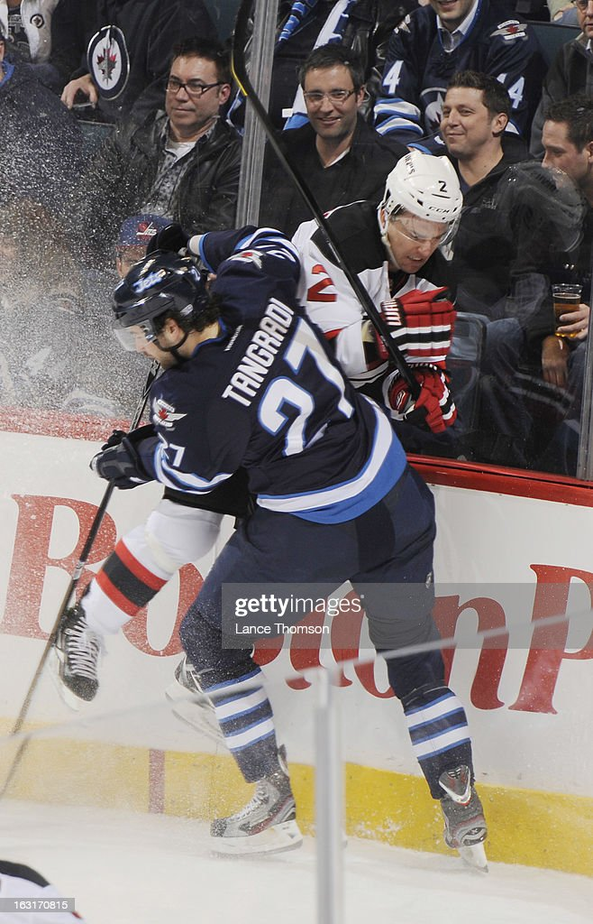 <a gi-track='captionPersonalityLinkClicked' href=/galleries/search?phrase=Eric+Tangradi&family=editorial&specificpeople=4361715 ng-click='$event.stopPropagation()'>Eric Tangradi</a> #27 of the Winnipeg Jets checks <a gi-track='captionPersonalityLinkClicked' href=/galleries/search?phrase=Marek+Zidlicky&family=editorial&specificpeople=203291 ng-click='$event.stopPropagation()'>Marek Zidlicky</a> #2 of the New Jersey Devils hard into the end boards during second-period action at the MTS Centre on February 28, 2013 in Winnipeg, Manitoba, Canada. The Jets defeated the Devils 3-1.