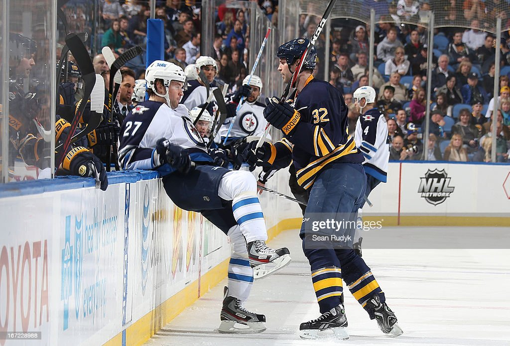 <a gi-track='captionPersonalityLinkClicked' href=/galleries/search?phrase=Eric+Tangradi&family=editorial&specificpeople=4361715 ng-click='$event.stopPropagation()'>Eric Tangradi</a> #27 of the Winnipeg Jets gets checked into the Sabres bench by John Scott #32 of the Buffalo Sabres at First Niagara Center on April 22, 2013 in Buffalo, New York.