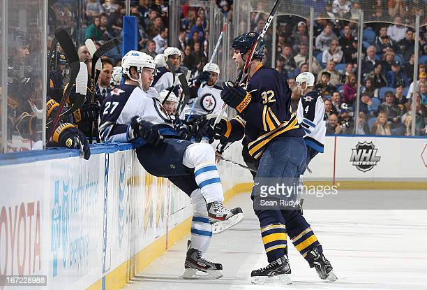 Eric Tangradi of the Winnipeg Jets gets checked into the Sabres bench by John Scott of the Buffalo Sabres at First Niagara Center on April 22 2013 in...