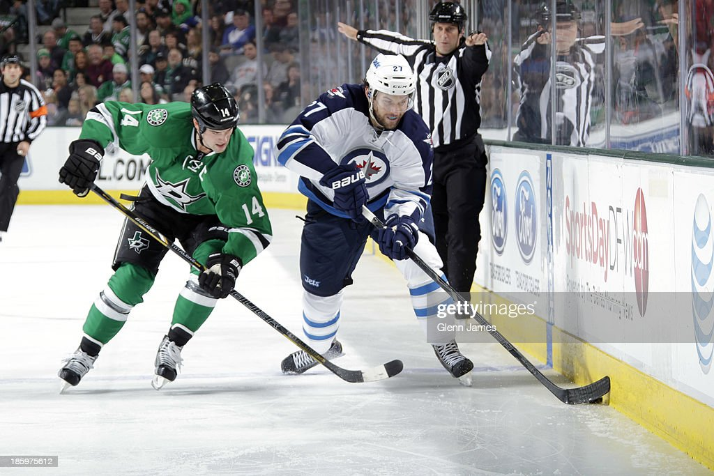 <a gi-track='captionPersonalityLinkClicked' href=/galleries/search?phrase=Eric+Tangradi&family=editorial&specificpeople=4361715 ng-click='$event.stopPropagation()'>Eric Tangradi</a> #27 of the Winnipeg Jets handles the puck against <a gi-track='captionPersonalityLinkClicked' href=/galleries/search?phrase=Jamie+Benn&family=editorial&specificpeople=4595070 ng-click='$event.stopPropagation()'>Jamie Benn</a> #14 of the Dallas Stars at the American Airlines Center on October 26, 2013 in Dallas, Texas.