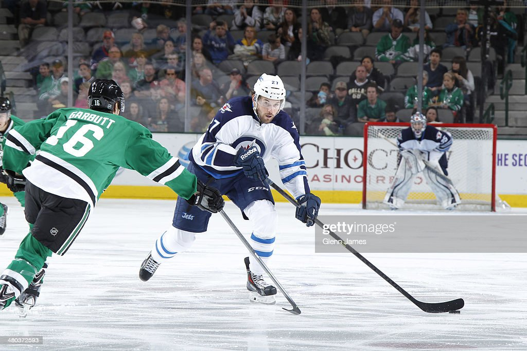 Eric Tangradi #27 of the Winnipeg Jets handles the puck against Ryan Garbutt #16 of the Dallas Stars at the American Airlines Center on March 24, 2014 in Dallas, Texas.