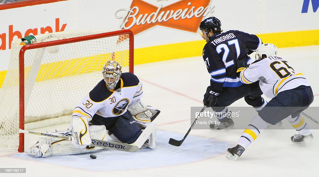 Eric Tangradi #27 of the Winnipeg Jets is checked from behind by Brian Flynn #65 of the Buffalo Sabres as they watch goaltender Ryan Miller #30 make a save during third period action at the MTS Centre on April 9, 2013 in Winnipeg, Manitoba, Canada. The Jets defeated the Sabres 4-1.