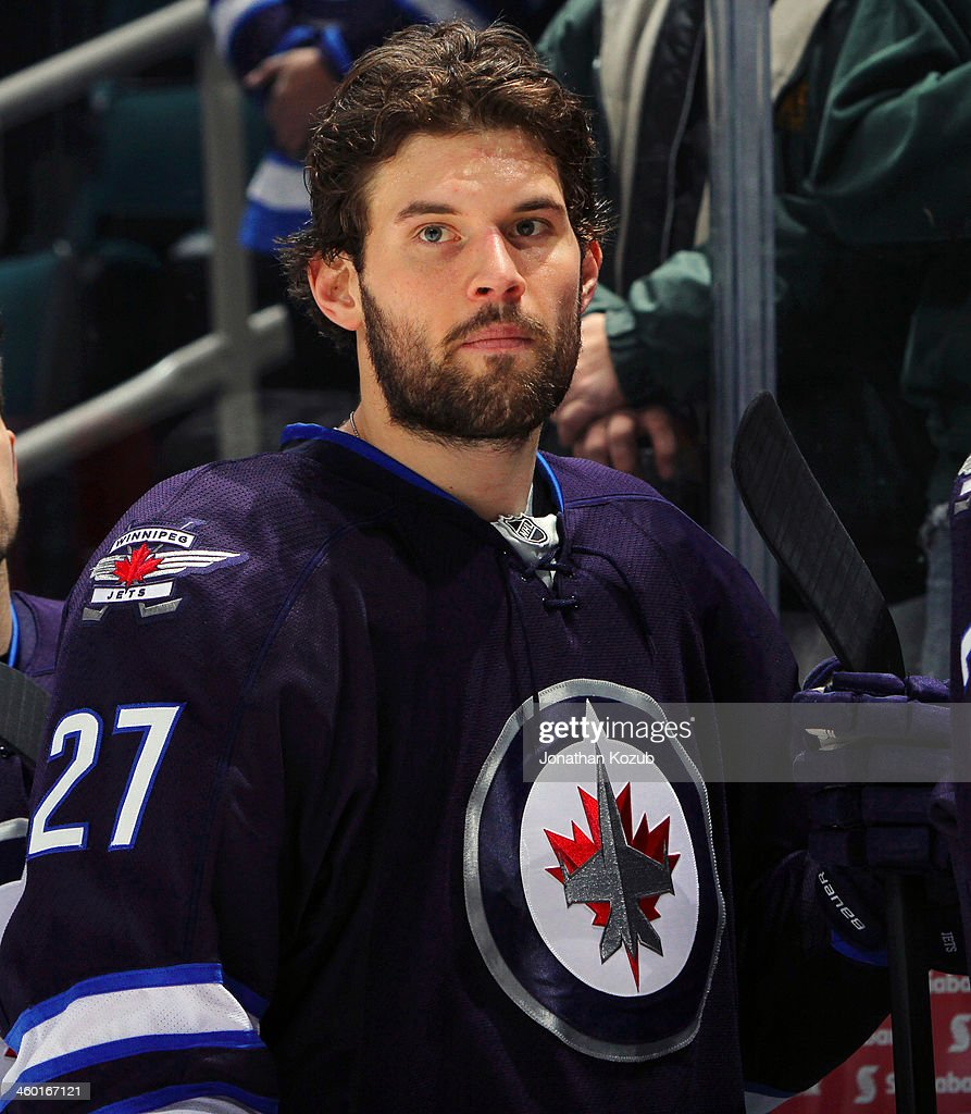 Eric Tangradi #27 of the Winnipeg Jets looks on from the bench during the singing of the National anthems prior to puck drop against the Florida Panthers at the MTS Centre on December 20, 2013 in Winnipeg, Manitoba, Canada.