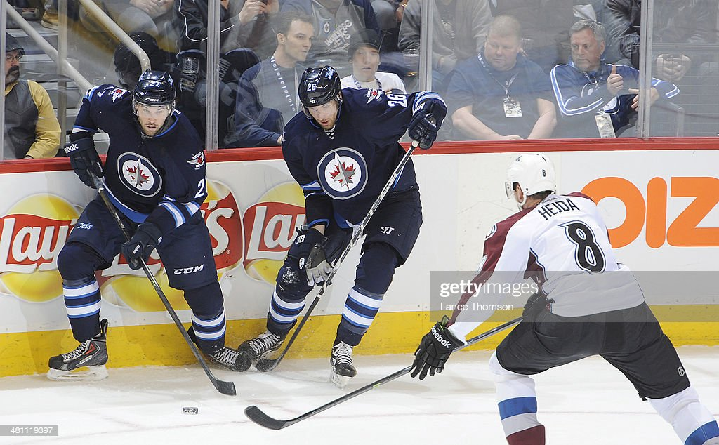 Eric Tangradi #27 of the Winnipeg Jets plays the puck alongside teammate Blake Wheeler #26 as Jan Hejda #8 of the Colorado Avalanche defends during second period action at the MTS Centre on March 19, 2014 in Winnipeg, Manitoba, Canada. The Jets defeated the Avs 5-4 in overtime.