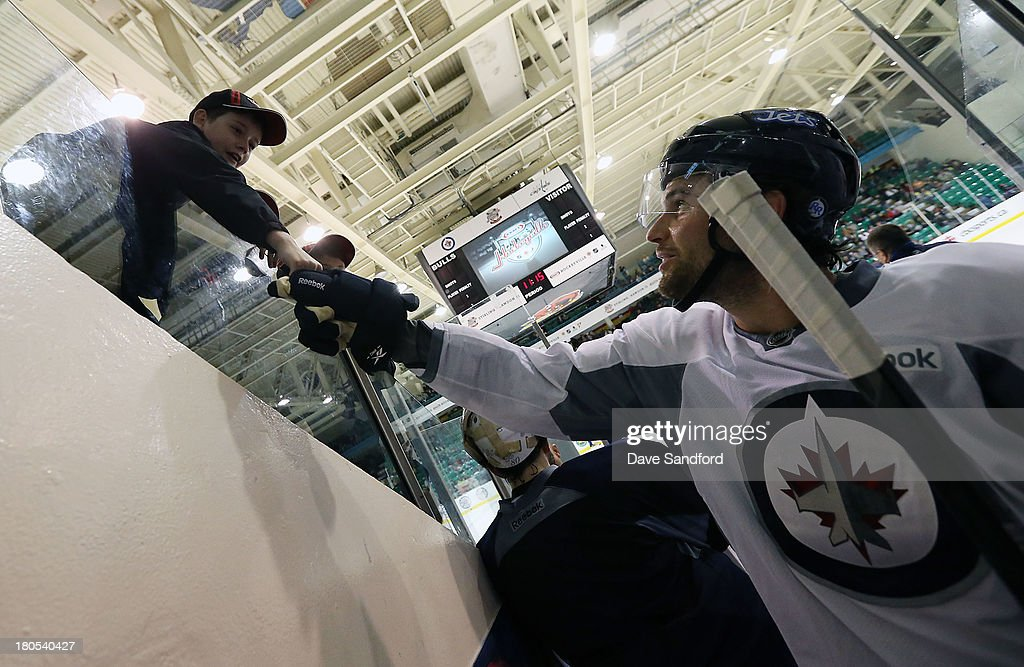 Eric Tangradi #27 of the Winnipeg Jets signs an autograph for a fan at Yardman Arena during Kraft Hockeyville Day 2 on September 14, 2013 in Stirling, Ontario, Canada.