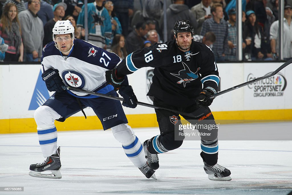 Eric Tangradi #27 of the Winnipeg Jets skates against Mike Brown #18 of the San Jose Sharks at SAP Center on March 27, 2014 in San Jose, California.