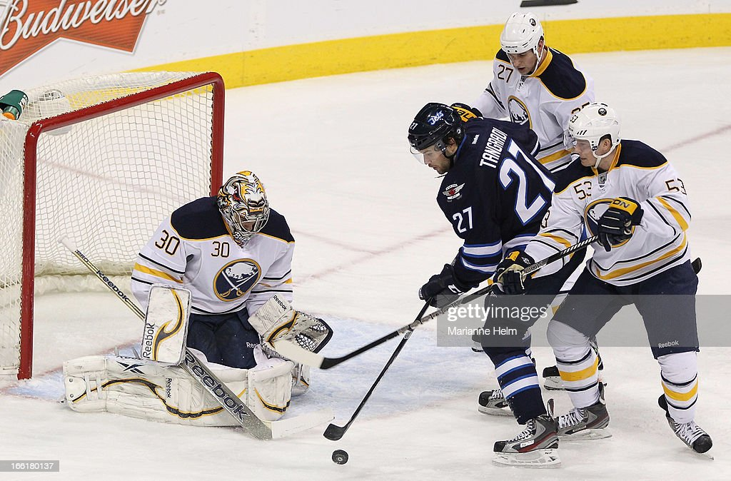 Eric Tangradi #27 of the Winnipeg Jets tries to get the puck past Adam Pardy #27, Mark Pysyk #53 and goalie Ryan Miller #30 of the Buffalo Sabres in first-period action against the Buffalo Sabres on April 9, 2013 at the MTS Centre in Winnipeg, Manitoba, Canada.