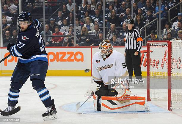 Eric Tangradi of the Winnipeg Jets tries to set a screen as the puck flies towards goaltender Viktor Fasth of the Anaheim Ducks during firstperiod...