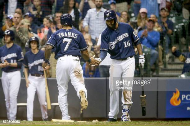 Eric Thames and Domingo Santana of the Milwaukee Brewers celebrate after Thames scored a run in the fourth inning against the Cincinnati Reds at...