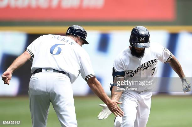 Eric Thames of the Milwaukee Brewers celebrates a home run with third base coach Ed Sedar during the third inning of a game against the San Francisco...