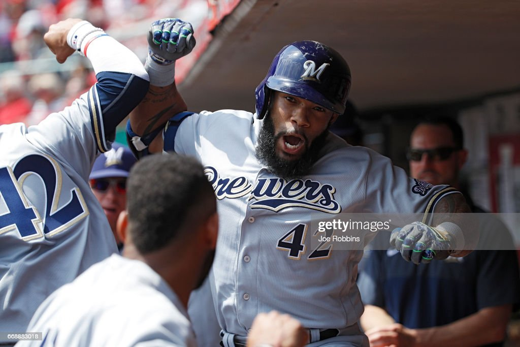 Eric Thames #7 of the Milwaukee Brewers celebrates in the dugout after hitting a solo home run to tie the game in the third inning against the Cincinnati Reds at Great American Ball Park on April 15, 2017 in Cincinnati, Ohio. All players are wearing #42 in honor of Jackie Robinson Day.