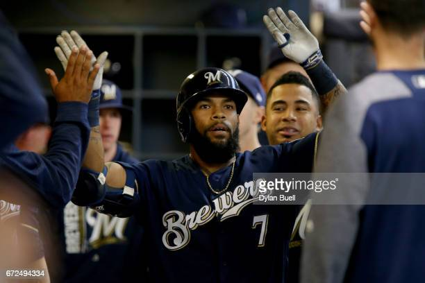 Eric Thames of the Milwaukee Brewers is congratulated by teammates after hitting a home run in the first inning against the Cincinnati Reds at Miller...