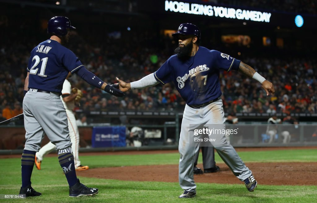 Eric Thames #7 of the Milwaukee Brewers is congratulated by Travis Shaw #21 after he scored on a sacrifice fly hit by Ryan Braun #8 in the seventh inning against the San Francisco Giants at AT&T Park on August 22, 2017 in San Francisco, California.