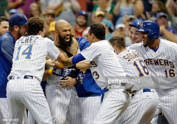 Eric Thames of the Milwaukee Brewers is mobbed by teammates after hitting a walkoff home run against the San Diego Padres during the tenth inning at...
