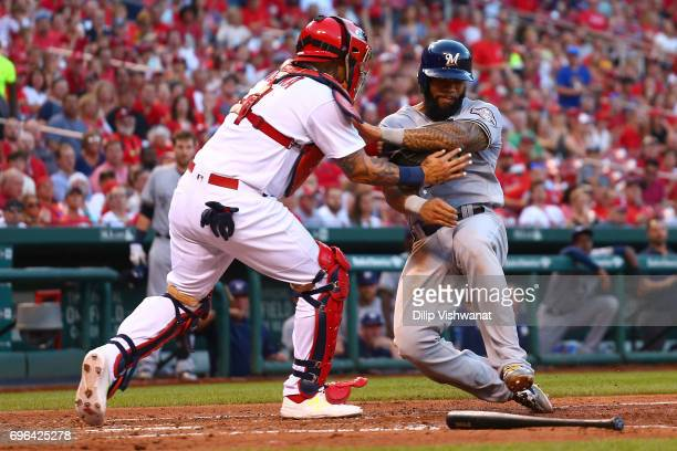 Eric Thames of the Milwaukee Brewers is tagged out at home pate by Yadier Molina of the St Louis Cardinals in the fifth inning at Busch Stadium on...