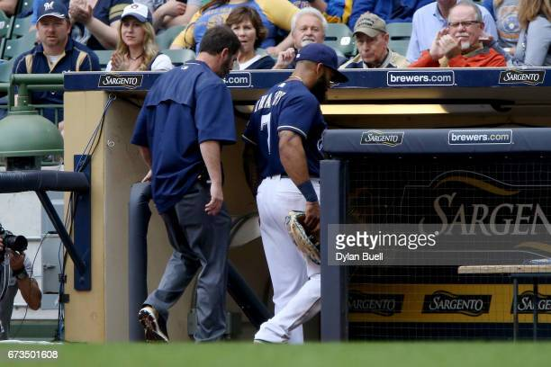 Eric Thames of the Milwaukee Brewers leaves the game with the athletic trainer in the eighth inning against the Cincinnati Reds at Miller Park on...