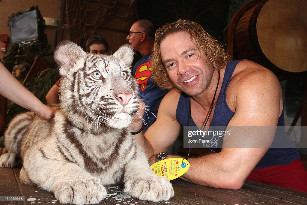 Eric 'the Trainer' Fleishman poses with a baby tiger at the Fun And Fit As A Family Sponsored By Carnival Featuring Goya Kidz Kitchen Hosted By Robert Irvine during the Food Network South Beach Wine & Food Festival at Jungle Island on February 22, 2014 in Miami, Florida.