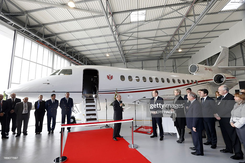 Eric Trappier (C) president of Dassault Aviation, speaks to Prince's Albert II of Monaco (6thR), his wife Princess Charlene (C, R) and Nice's Mayor Christian Estrosi (3rdR) on March 4, 2013 during the presentation of the Monegasque Princely family's new 'Falcon 7X' plane in its hangar at the Nice airport, southeastern France.