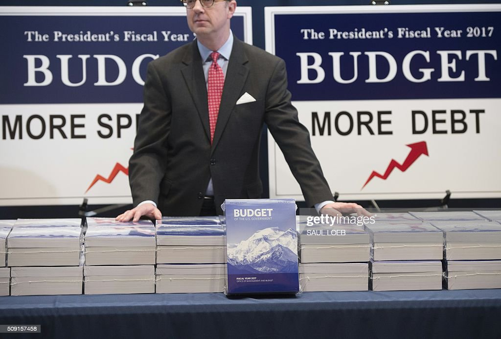Eric Ueland of the Senate Budget Committee distributes copies of US President Barack Obama's Fiscal Year 2017 budget on Capitol Hill in Washington, DC, February 9, 2016. / AFP / Saul LOEB