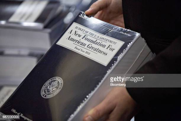 Eric Ueland Republican staff director with the Senate Budget Committee holds a copy of US President Donald Trump's fiscal 2018 budget proposal in the...