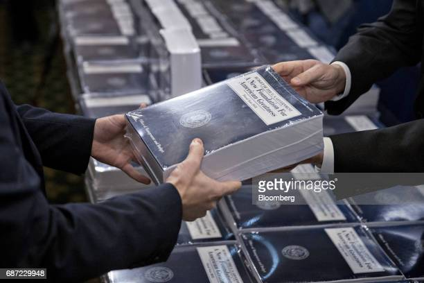 Eric Ueland Republican staff director with the Senate Budget Committee right hands a copy of US President Donald Trump's fiscal 2018 budget proposal...