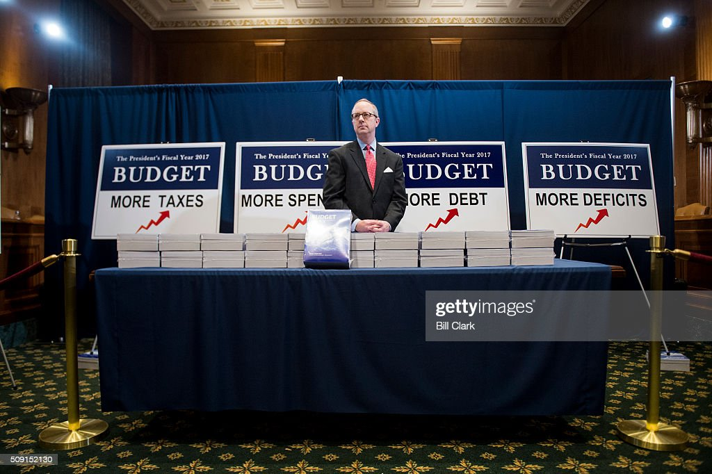 Eric Ueland, staff director for the Senate Budget Committee, poses for news photographers during a staged photo-op with printed copies of the Presidents FY2017 Budget in the Senate Budget Committee hearing room in the Dirksen Senate Office Building on Tuesday morning, Feb. 9, 2016.