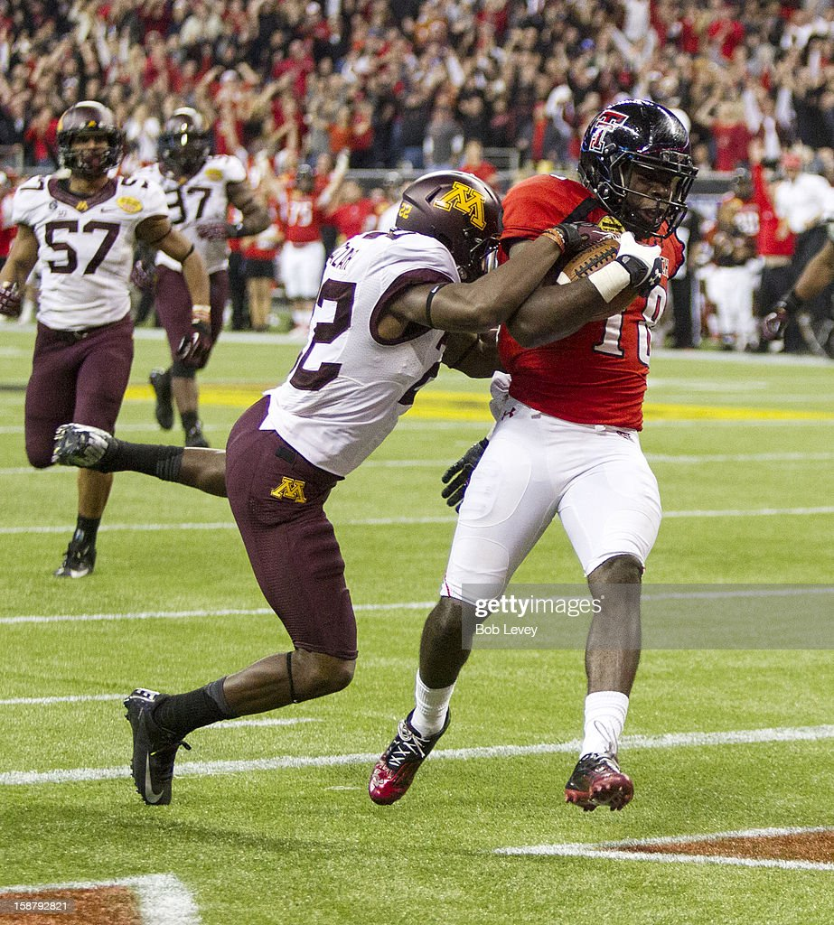 Eric Ward #18 of the Texas Tech Red Raiders scores as he drags Jeremy Baltazar #22 of the Minnesota Golden Gophers into the endszone during the Meineke Car Care of Texas Bowl at Reliant Stadium on December 28, 2012 in Houston, Texas. Texas Tech defeated Minnesota 34-31.