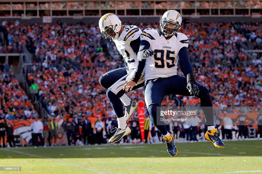 Eric Weddle #32 of the San Diego Chargers celebrates his 23 yard interception for a touchdown with Shaun Phillips #95 of the San Diego Chargers against the Denver Broncos in the first quarter at Sports Authority Field at Mile High on November 18, 2012 in Denver, Colorado.