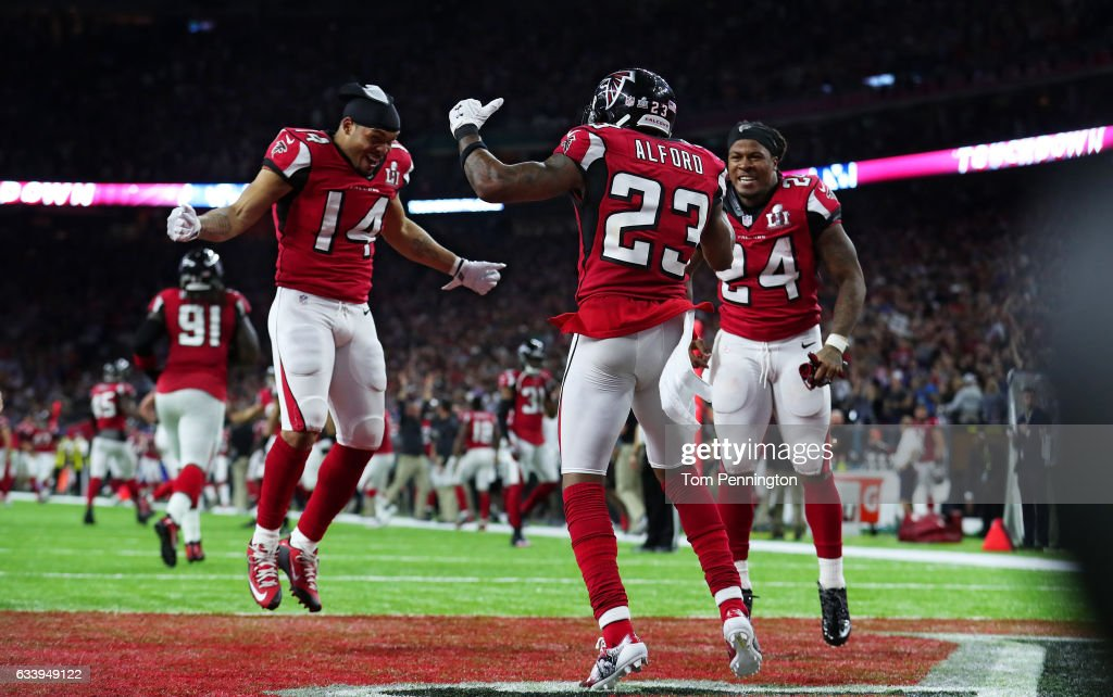 Eric Weems #14, and Devonta Freeman #24 celebrate with Robert Alford #23 of the Atlanta Falcons after Alford scored a touchdown on a 82 yard interception against the New England Patriots during Super Bowl 51 at NRG Stadium on February 5, 2017 in Houston, Texas.